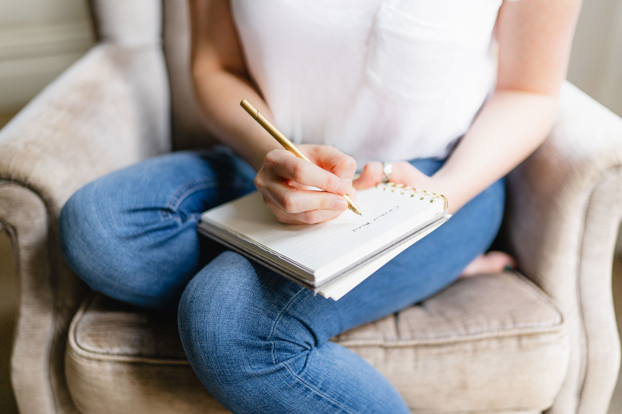 Woman wearing a white top and jeans sitting on a brown sofa with a notebook and pencil in hand. Her face isn't visible.