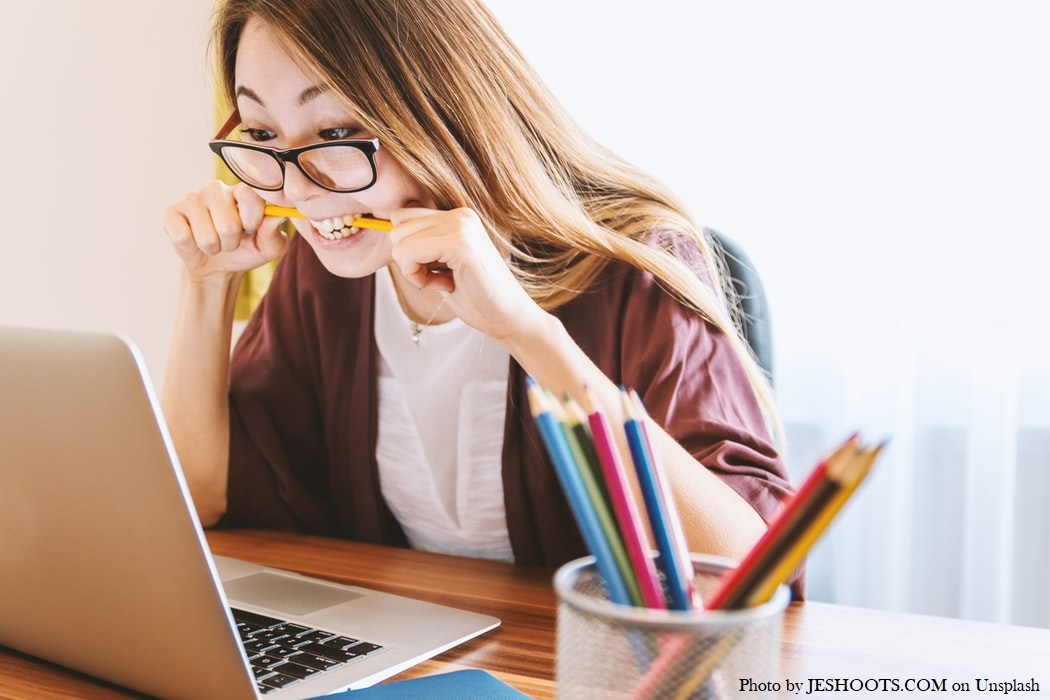 Stressed woman chewing on a pencil and staring at a computer