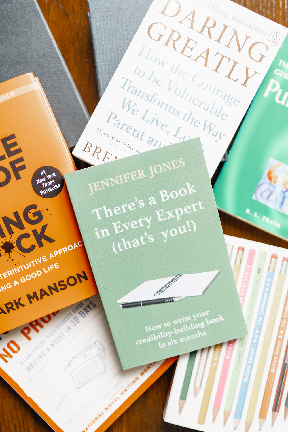 Books scattered on a table. The one on top is There's a Book in Every Expert (that's you!). Other titles include The Subtle Art of Not Giving a F*ck, Daring Greatly, No Plot? No Problem, The Penguin Guide to Punctuation, and The Craftsman