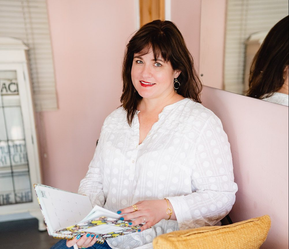 I'm sitting on a padded bench in a café. I have long dark hair with a fringe and am wearing a white long sleeve shirt and jeans with holes in both knees. I'm smiling at the camera and holding a book. There are two cushions on the bench - one yellow and one cream. The walls are light pink and there's a mirror behind my head.