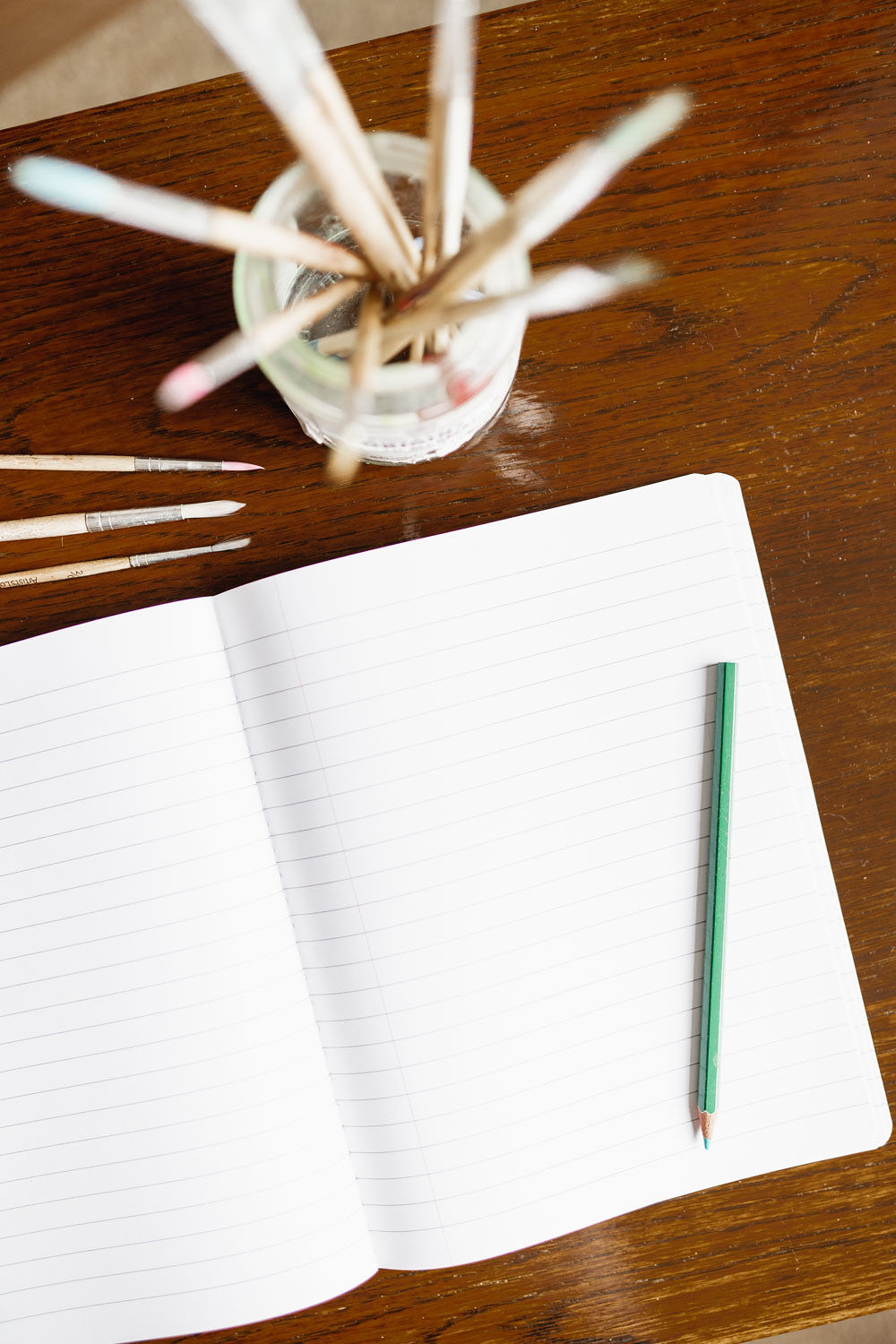 An open notebook with a green pencil lying over the right-hand page. Above the notebook are 4 paintbrushes of various sizes (parallel to the top of the notebook) and a jar containing several more brushes. Photograph taken from above.