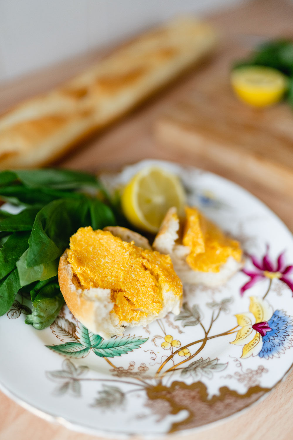 A plate with Victorian floral design. On it is a snack of bread with carrot hummus garnished with fresh basil and lemon.