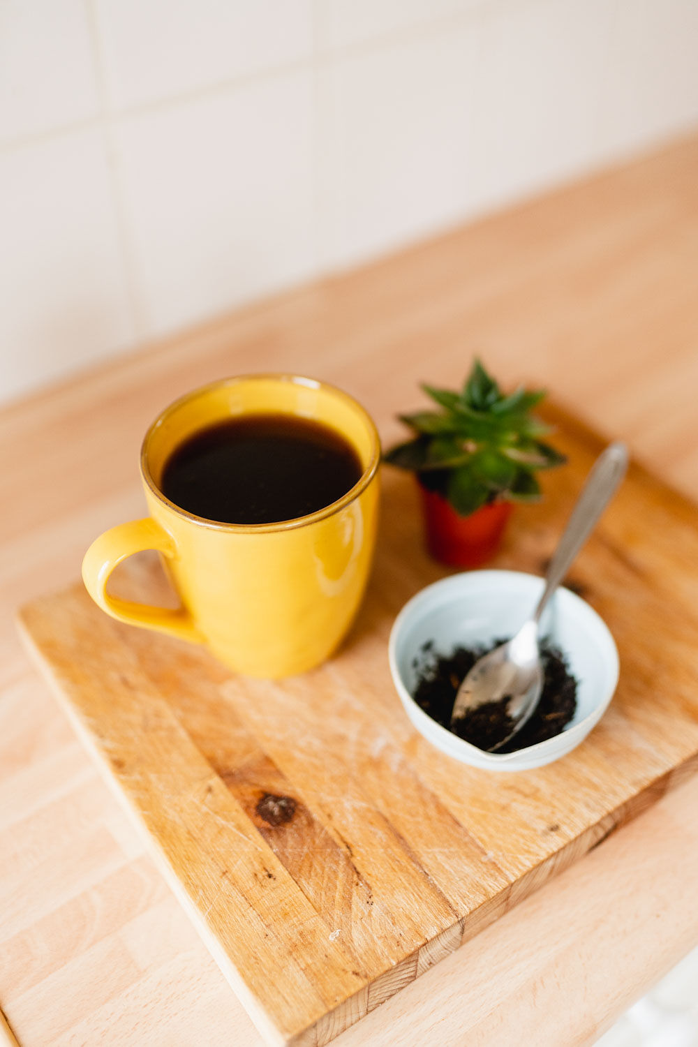 Yellow mug with tea on a wooden chopping board next to a small bowl of loose leaf tea and a small succulent - perfect for a writing ritual.
