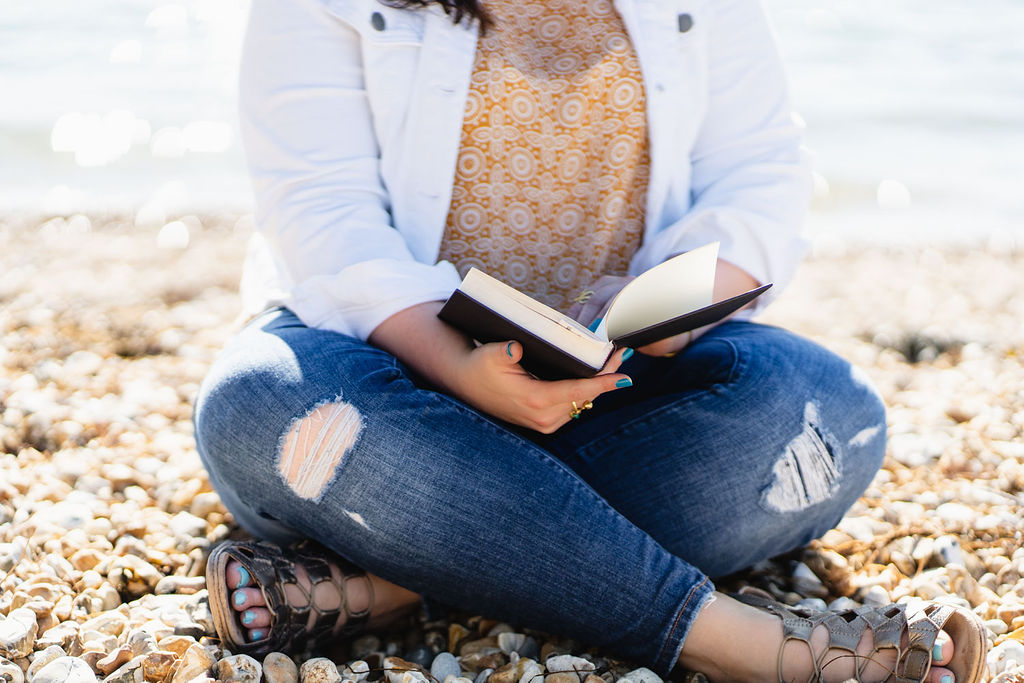 Woman (me) sitting cross legged on Southsea beach. I'm wearing a yellow shirt, white jacket, and blue jeans with holes in the knees. I'm holding an open book. It's sunny outside. My head/face are not in the shot - the focus is on the book.