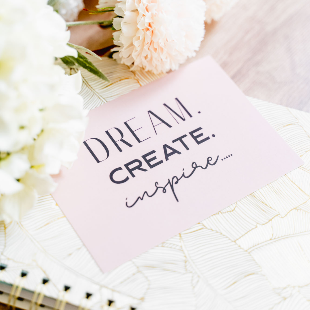 A pink card that reads 'Dream, Create, Inspire' sitting on a white notebook on a wooden table with two cream coloured carnations above.