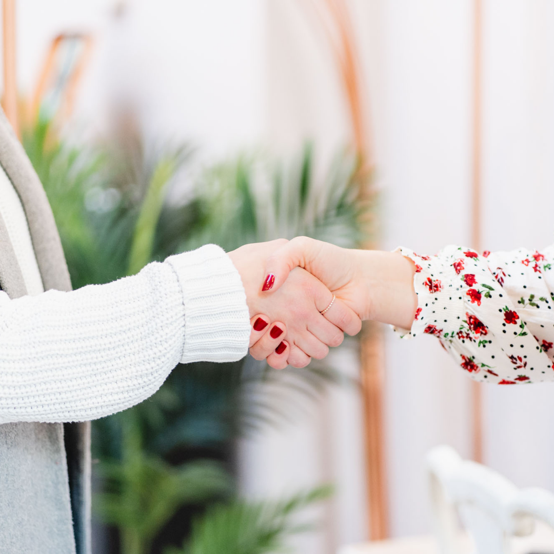 Two women shaking hands - focus on their hands. One has red nail polish and is wearing a white top with a red print. The other is wearing a white top.