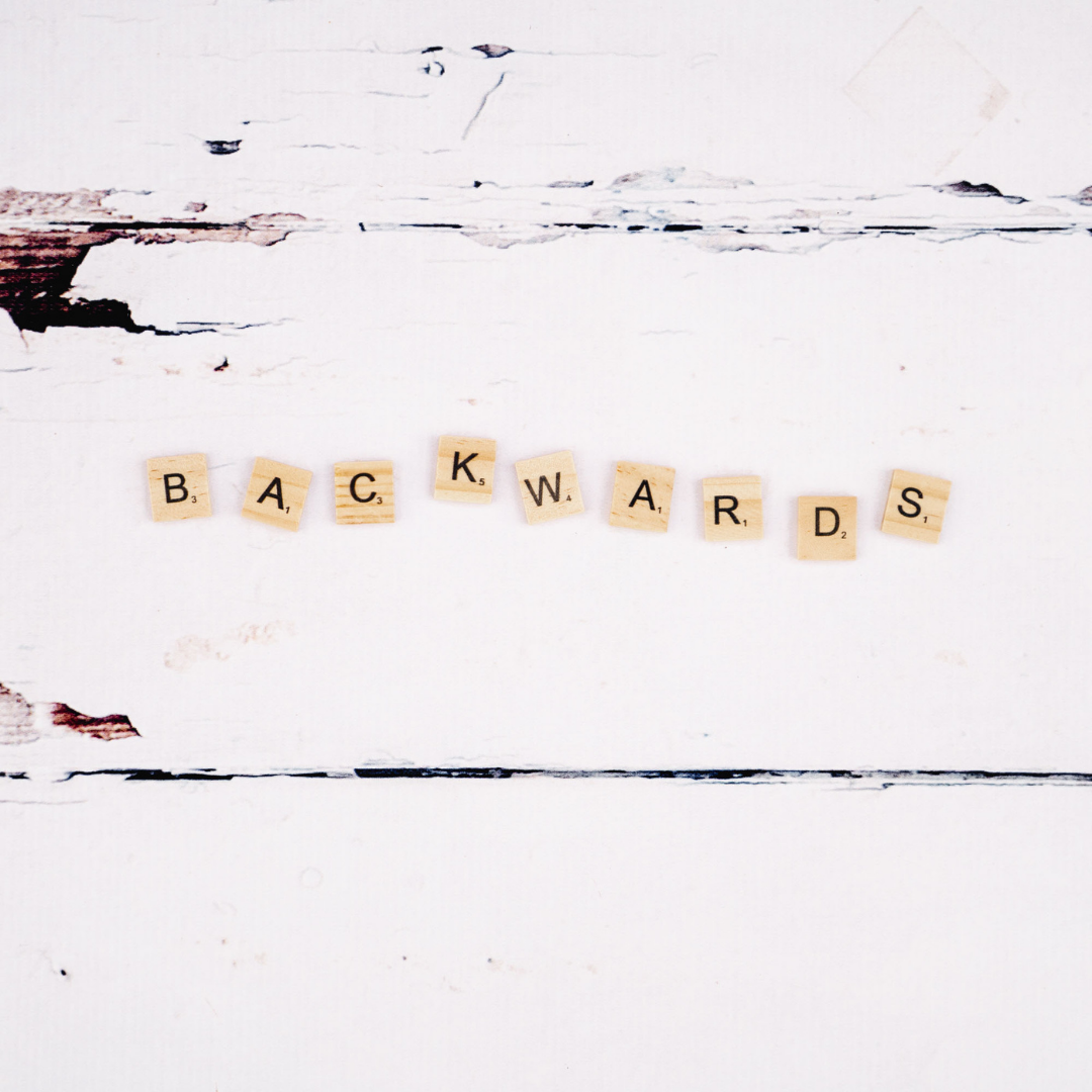 """""""Backwards"""" spelled out in scrabble tiles on a white table."""