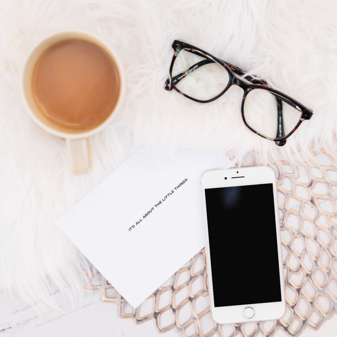 White card that reads 'It's all about the little things' next to a smart phone, pair of glasses, and mug of tea on a light background.
