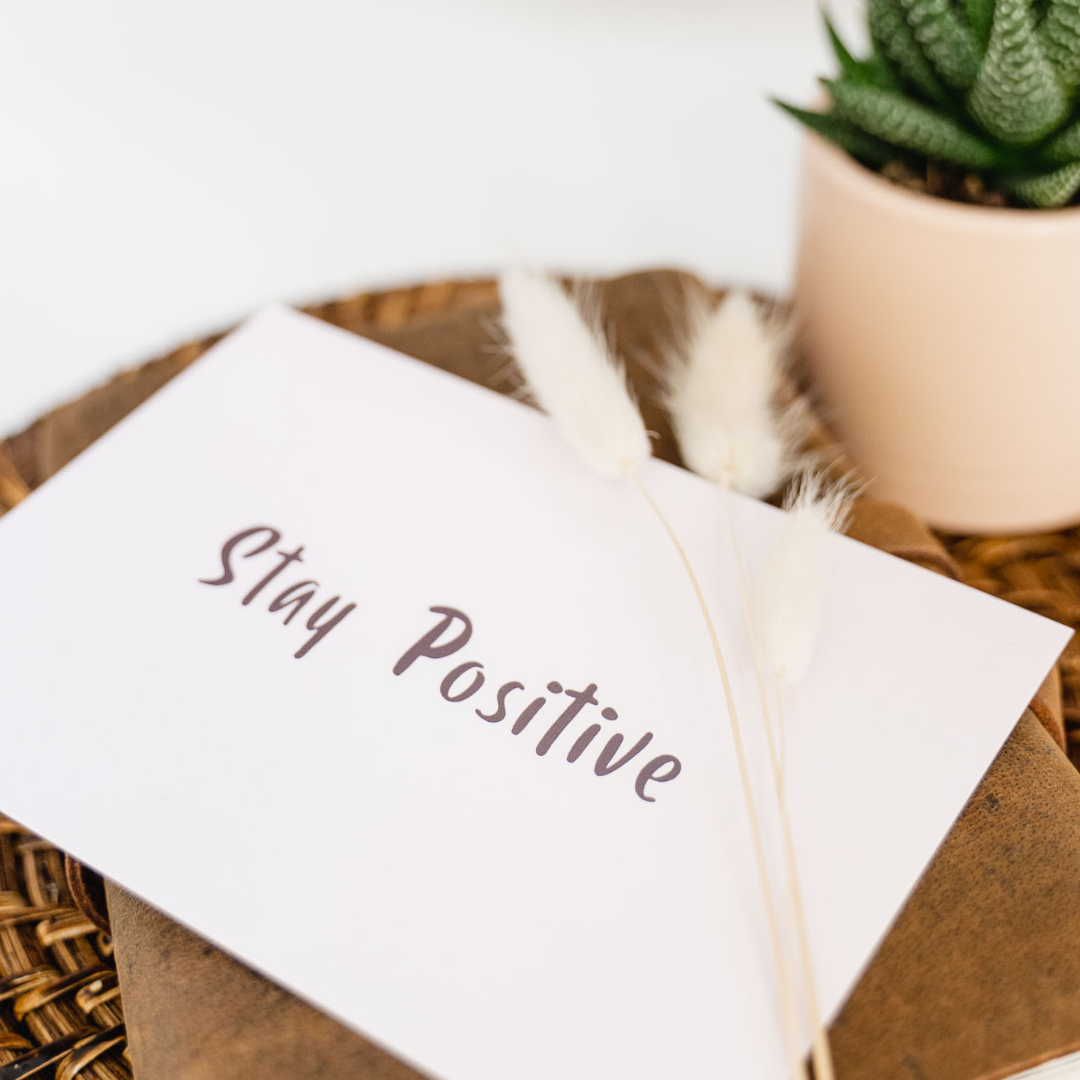 White card that says 'Stay positive' on a brown table next to a small potted plant.